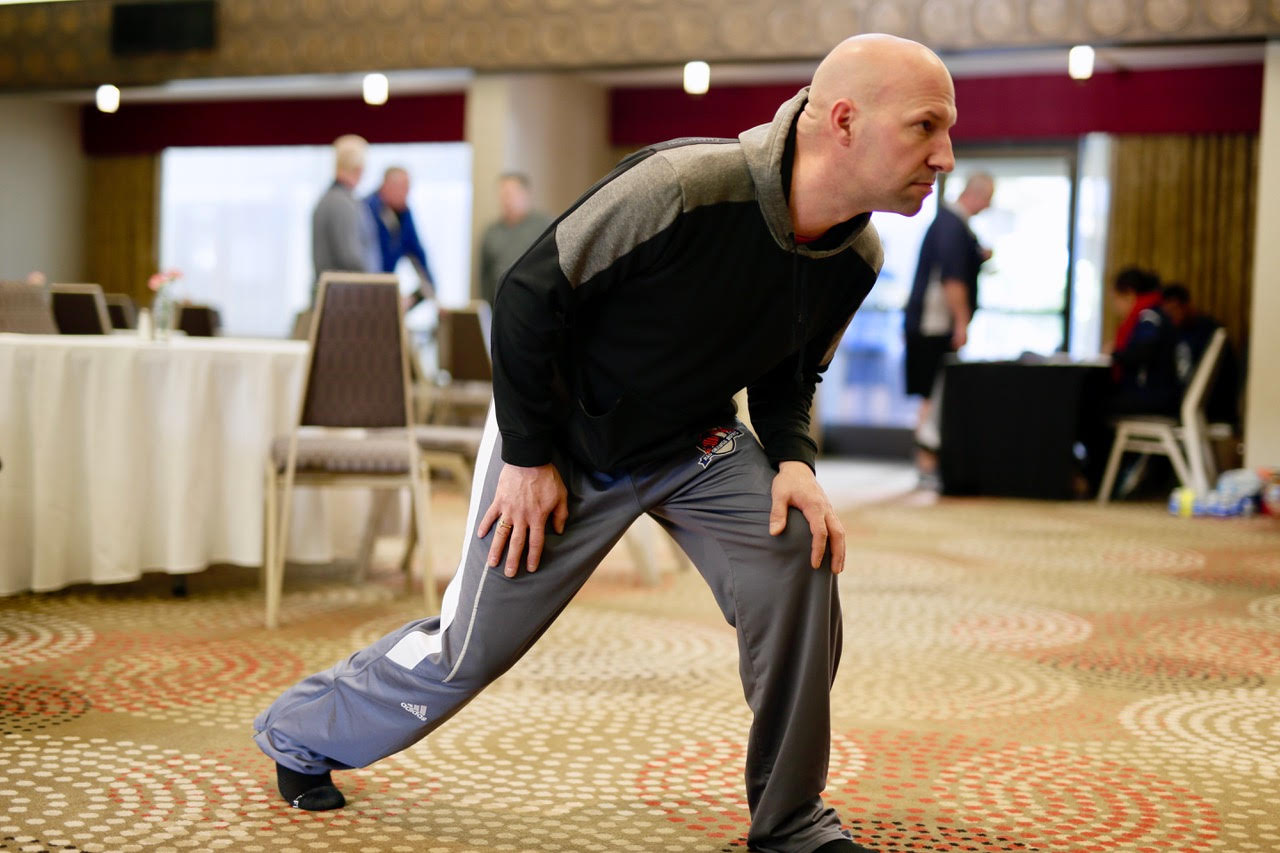 Baseball sports official doing a mobility stretch